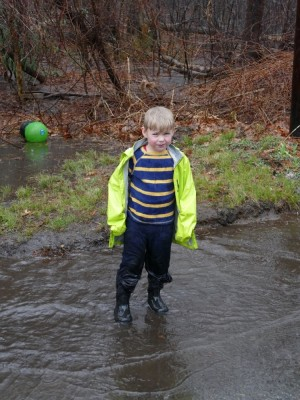 Zion standing in a puddle in the pouring rain