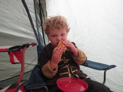 Harvey eating a bagel in the tent porch