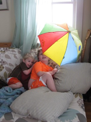 the boys in their swimsuits on the couch with an open umbrella