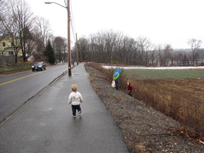 the boys walking on the sidewalk by a fallow field