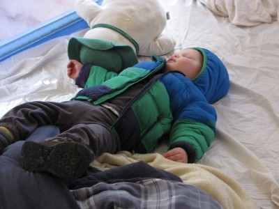 Lijah sleeping on his back in the bed, still wearing boots and coat