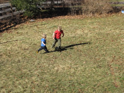 Harvey and Zion, in short sleeves, playing soccer in the snow-free yard