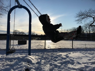 Lijah swinging at the playground with the low sun behind him