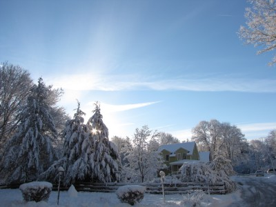 our snowcovered house and yard in the early morning light