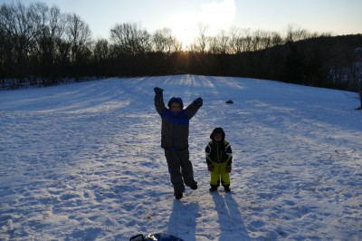 Harvey and Zion posing on the sledding hill as the sun sets