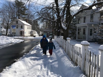 Harvey and Zion walking on the snowy sidewalk by a white picket fence