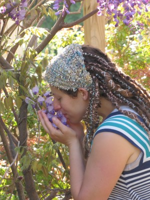Leah smelling a wisteria flower