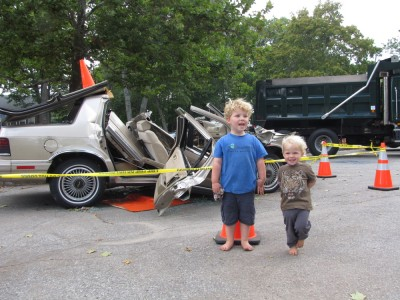 Harvey and Zion saying cheese in front of a car destroyed in a life-saving demonstration