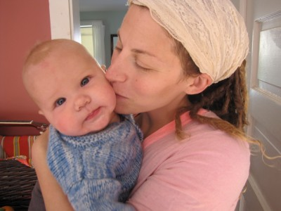 Leah holding Lijah, kissing him on the cheek