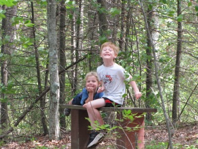Zion and Nathan posing on a bench in the woods