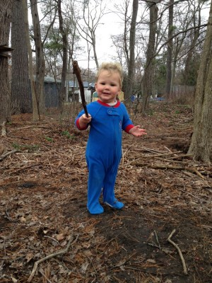 Lijah playing in the woods in his footie pajamas