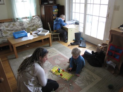 Harvey working at his desk, Zion and Mama playing a board game