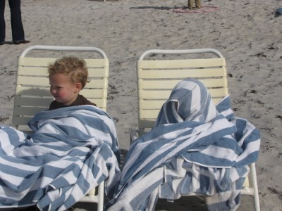 Lijah and Zion on beach chairs wrapped in towels