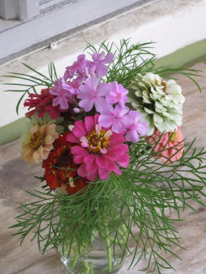 a small bouquet of flowers in a half-pint jar