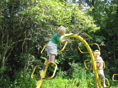 Zion and Harvey playing on a yellow metal climbing structure