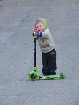Lijah in his Yoda sweatshirt on his green scooter