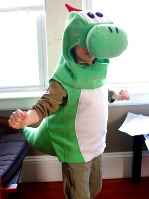Bruce modeling the Yoshi costume indoors