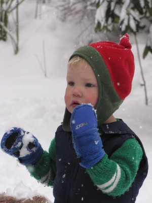 Lijah in his cute red hat eating snow