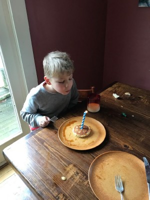Zion blowing out a candle stuck in a pancake