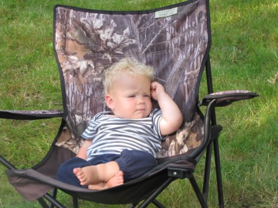 Zion lounging in an adult-size camping chair