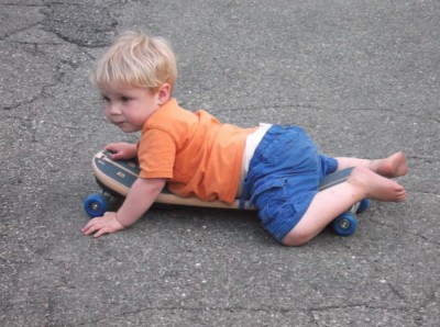 zion on his belly on a skateboard in the street
