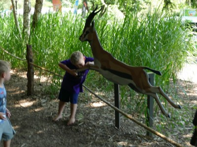 Zion pretending to eat the leg of a wooden antelope