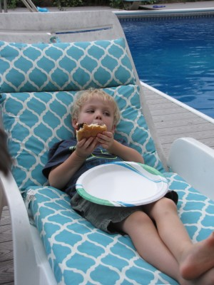 Zion relaxing in a chair by the pool eating a hamburger