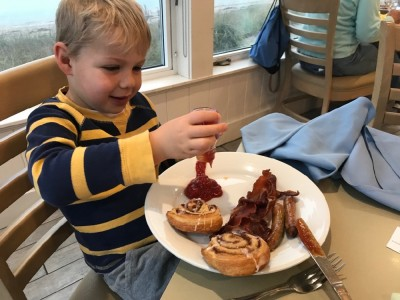 Zion pouring ketchup onto his plate of sausages, bacon, and danishes