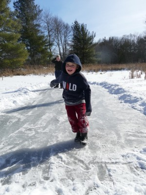 Zion sliding on a small cleared patch of ice on a snowy marsh